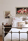 Floral pillows and scatter cushions on nostalgic metal bed below framed painting of roses