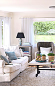 Seating area in country house living room in front of panoramic window with view of garden