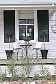 Playful bistro chairs and table in front of wooden facade and windows with dark shutters; lollipop trees in black metal planters