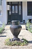 Brunnen in Form einer anthrazitfarbenen Amphore auf dem Kiesweg vor einer Hauseingangstür