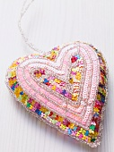 A fabric heart decorated with sequins on a white surface