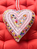 A fabric heart decorated with sequins on a red surface