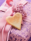 A gift box decorated with a bow, roses and a heart-shaped biscuit
