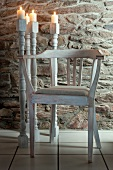 Candlesticks made of old table legs and chair against stone wall