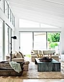 Helle Polstergarnitur und Tisch aus Metall in modernem Wohnzimmer in zeitgenössischem Glas-Stahl Anbau