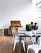 Retro-look metal chairs and simple wooden table on terrace with wooden floor