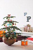 Decorated Christmas tree in bowl and orange glass lantern on wooden floor in front of dog sitting on pale sofa