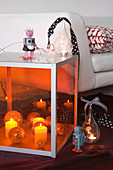 Lit candles and Christmas baubles in large floor lantern with orange glass next to sofa with pale upholstery