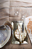 Cutlery with mother-of-pearl handles on silver dish next to large shell on table cloth
