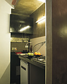 Small hidden kitchen in Roman studio apartment with walls painted using artistic structured technique