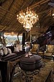 Elegante Antikmöbel und Kronleuchter in rustikalem Haus mit Strohdach