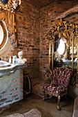 Elegant rococo armchair in front of gilt-framed mirror on brick wall of bathroom