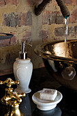 Water running into brass sink on washstand against brick wall