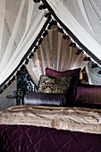 Four-poster bed with canopy and view of scatter cushions with elegant velvet covers