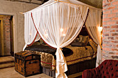 Four-poster bed with canopy and shiny gold bedspread in bedroom with exposed brick walls
