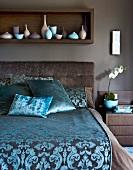 Elegantes Bett mit gemustertem Satinbezug vor braun getönter Wand