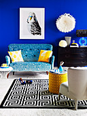 Picture of bird above blue sofa, ornaments on chest of drawers and black and white patterned rug in living room with blue wall