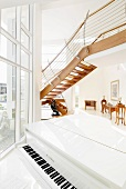 White, shiny piano in a split level living room with open designer stairs in front of floor-to-ceiling windows