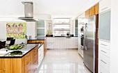 Küchenblock und übergrosser Edelstahlkühlschrank in breiter, offener Küche mit Fronten in Weiss und Holz