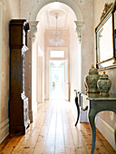 Long hallway with simple wooden flooring, arch and antique furniture
