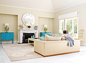 Pair of pastel blue, antique chests of drawers either side of open fireplace in traditional living room with two large couches