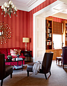 Traditional living room in warm shades of red with deep pink couch and adjoining library