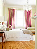 Cheerful pink and brown curtains in traditional bedroom with crystal chandelier and simple wooden floor