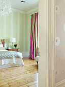 Pale green bedroom with simple wooden floor and colourful curtains with pink stripes