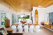 White, retro shell chairs at dining table in open-plan, contemporary interior