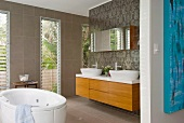 Modern bathroom with free-standing bathtub in front of floor-to-ceiling window