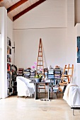 Workspace in niche of living room in front of half-height bookshelves and easel