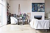 Chaiselongue mit weißem Überwurf vor offenem Kamin und Nische mit Arbeitstisch vor Bücherregal in schlichtem Wohnraum