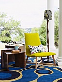 Yellow, upholstered chair on a modern rug with a distinct pattern on a veranda with Doric columns