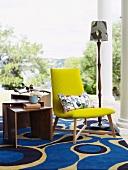 Gelber Polsterstuhl auf modernem Teppich mit klarem Muster auf Veranda mit dorischen Säulen