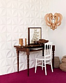Antique bureau and white chair against white, three dimensional wall panels and on purple carpet