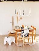 Hocker und Stühle an gedecktem Esstisch unter Deckenkerzenleuchter aus Hirschgeweihen