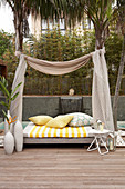 Daybed with fabric canopy hung between palm trees on modern wooden terrace