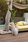 Collection of vases on floor of wooden terrace next to modern daybed with fabric canopy hung between palm trees