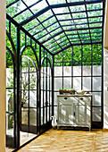 Wintergarten-Anbau in dunkler Metallkonstruktion mit antiker Kommode und Holzparkett