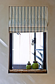 Antique, green glazed, ceramic containers and striped Roman blind at a window with outward opening windows