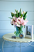 Bouquet of spring flowers on vintage metal table against blue wooden wall
