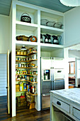 Kitchen with open-fronted shelves and integrated pantry next to fridge combination