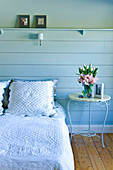 Bed with white country-style bed linen and vintage, metal side table against blue wooden wall