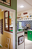 View into open-plan, colourful kitchen with partition wall separating hallway