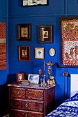 Antique chest of drawers in corner of bedroom below framed pictures on walls painted Yves Klein Blue