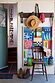 Straw hat and gardening utensils hanging on coat rack in rustic foyer