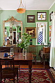 Dark wood dining table and chairs in Art Nouveau living room with green-painted walls