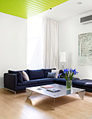Dark corner sofa and metal coffee table in bright living room