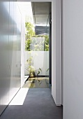 Narrow courtyard at side entrance of contemporary house with view of pool in garden