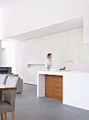 Woman at white designer kitchen counter in front of fitted cupboards in open-plan interior